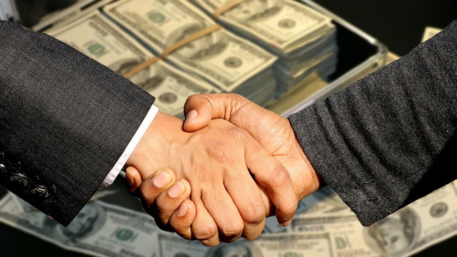 business acquisition deal money handshake