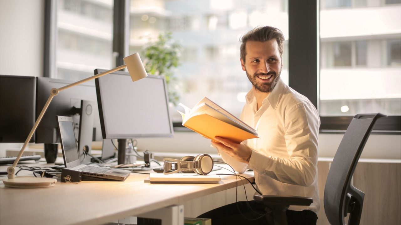 male business owner holding a notebook at a desk